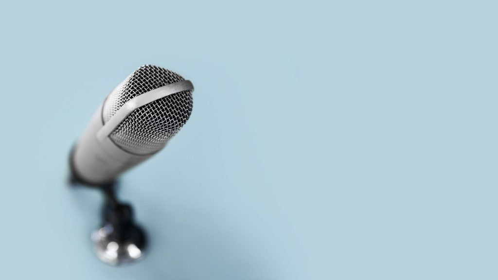 podcast microphone on a plain blue background